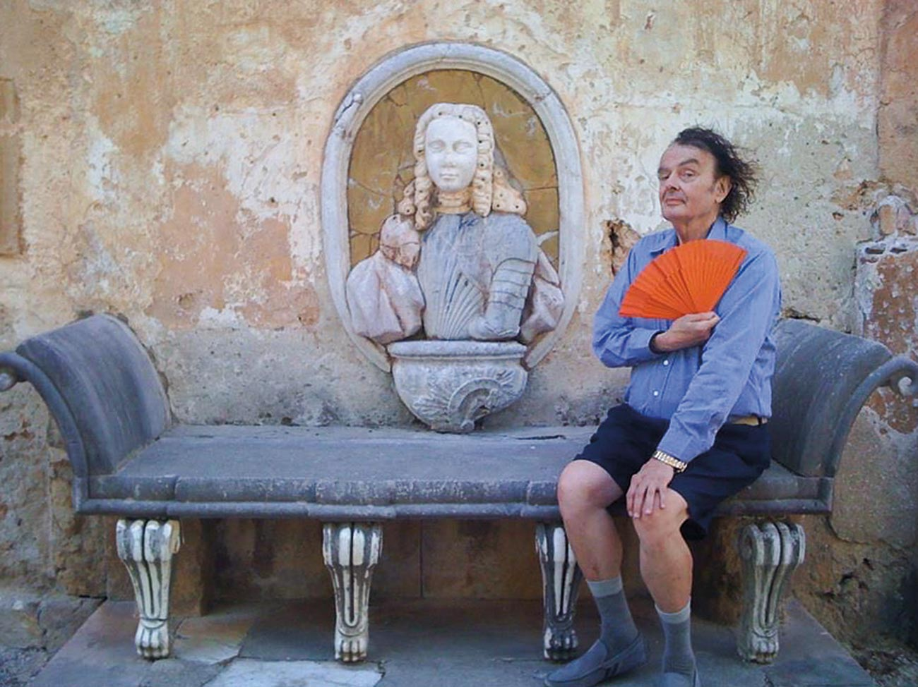 Ira posing with orange fan next to garden bust on stone bench